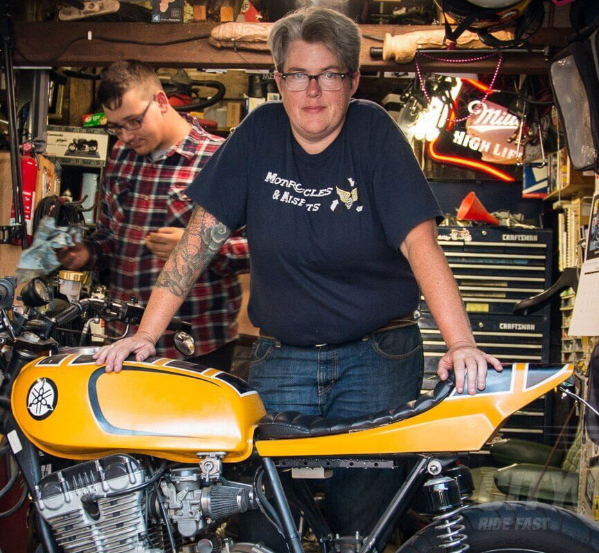 Liza Miller standing at Recycle Santa Cruz with a yellow motorcycle. She is the tour leader of Chickistan, an all-women motorcycle tour to Pakistan.